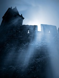 Moonlit gothic scenery with remote mysterious european medieval castle