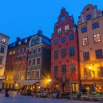 """Stockholm, Sweden - 5th April 2012: The vibrant villas and quaint restaurants of historic Stortorget, Great Square, the iconic landmark plaza on Gamla Stan gently illuminated against the blue dusk sky in the heart of Stockholm."""